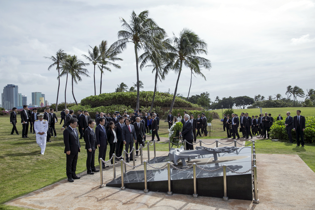 Japanese Prime Minister Shinzo Abe, center, and delegation bow at the Ehime Maru Memorial at Kakaako Waterfront Park, Monday, Dec. 26, ...