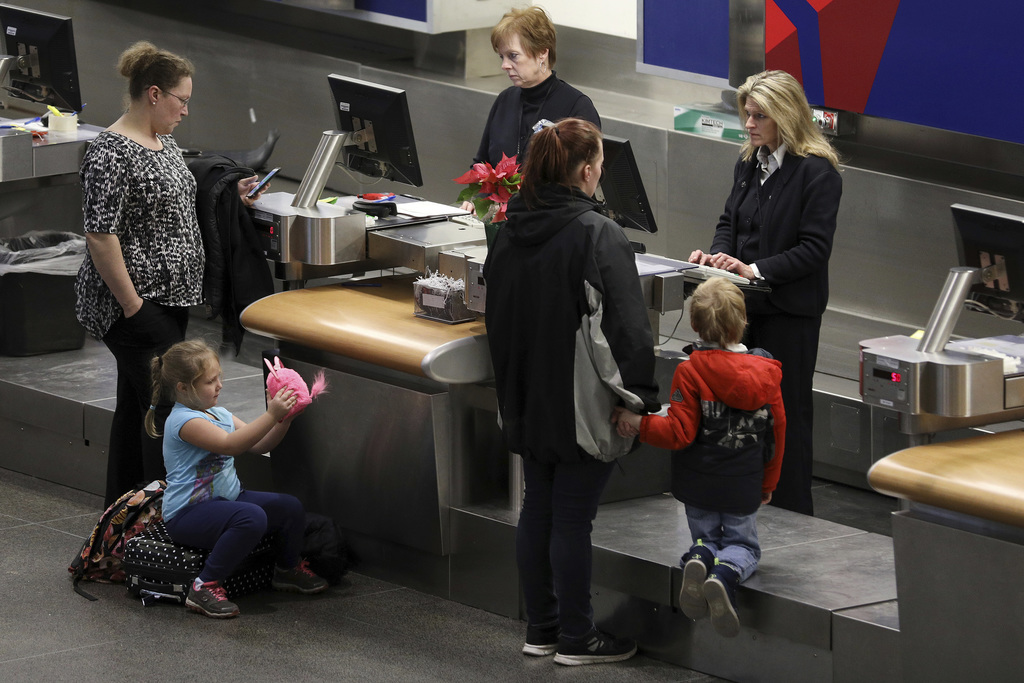 A young girl plays with a plush toy at the Delta Air Lines counter after several flights were delayed or canceled mostly due to weather...