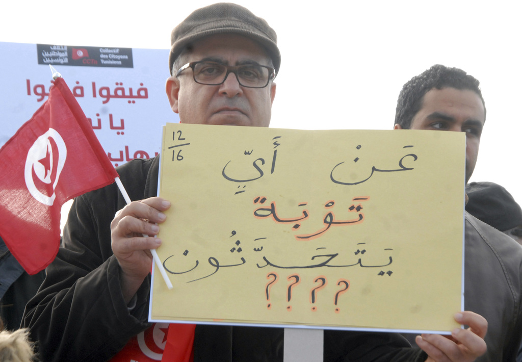 A man holds a poster reading 'What pardon are you talking about?' during a demonstration outside the Tunisian parliament, in Tunis, Sat...