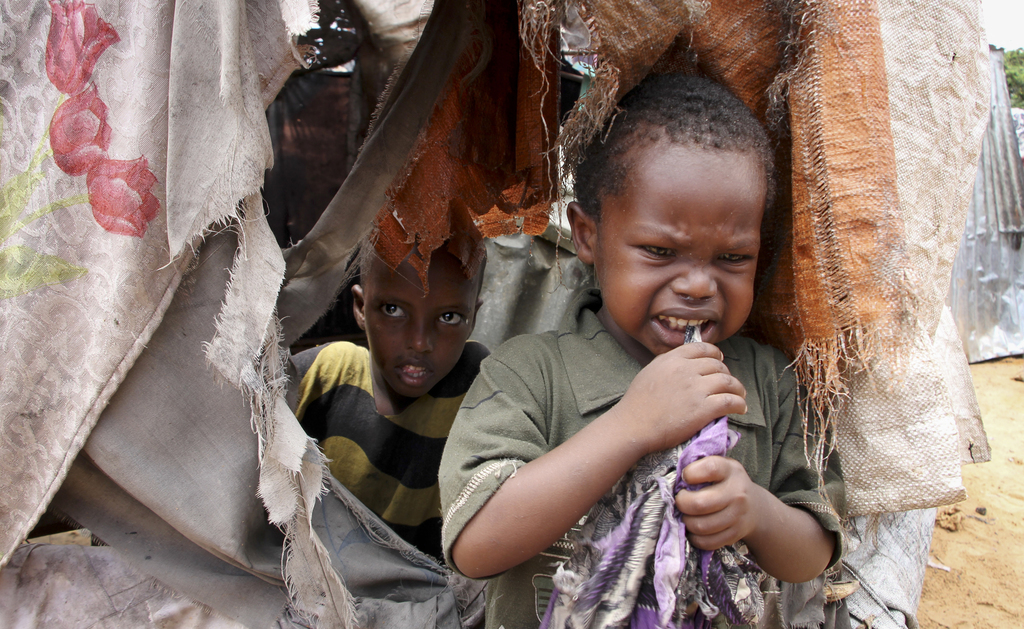 In this photo taken Wednesday, Nov. 16, 2016, Somali children who were repatriated to Somalia from Kenya's Dadaab camp, stand by their ...