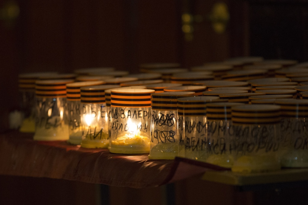 The names of  the victims of a military choir and St. George's ribbons are placed on candles, in front of the Alexandrov Ensemble build...