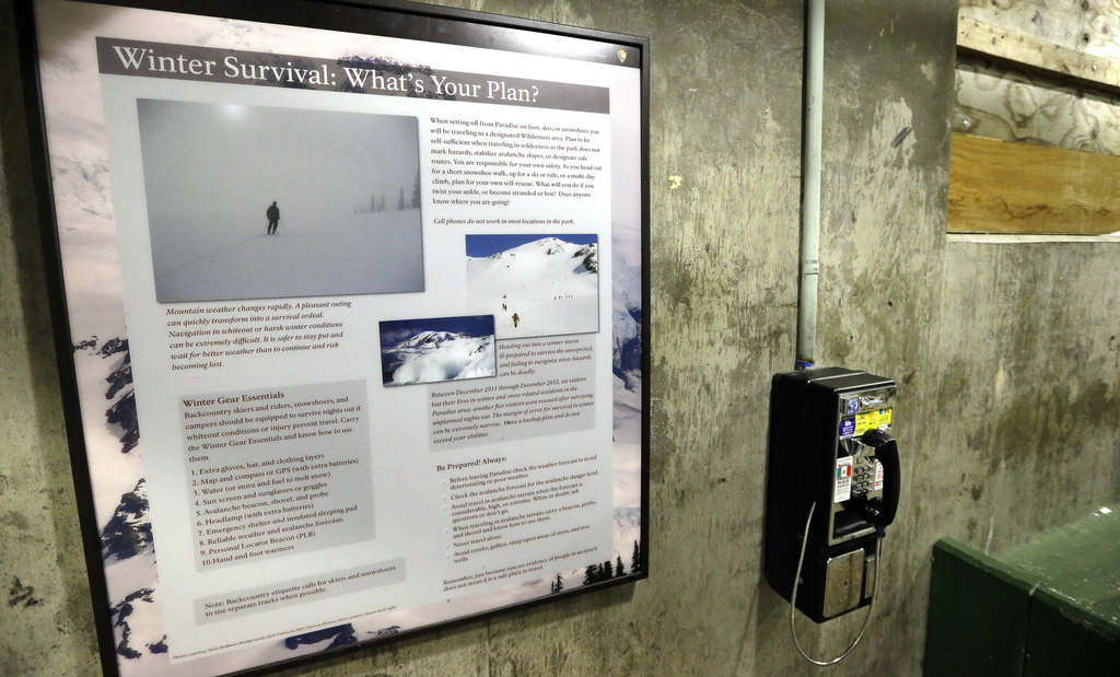 In this photo taken Friday, Dec. 16, 2016, a sign advises visitors on winter survival skills next to a pay phone at the Paradise area a...