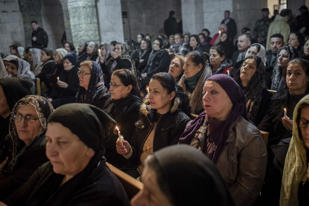 People attend Christmas Eve's Mass in the Assyrian Orthodox church of Mart Shmoni, in Bartella, Iraq, Saturday, December 24, 2016. For ...