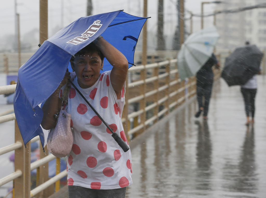 People brave the rain and wind brought about by typhoon Nock-Ten a day after Christmas Monday, Dec. 26, 2016 at suburban Paranaque city...