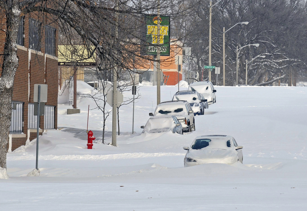 Bismarck's Second Street in the downtown area had cars stuck in snowdrifts Monday, Dec. 26, 2016, in Bismarck, N.D. The combination of ...