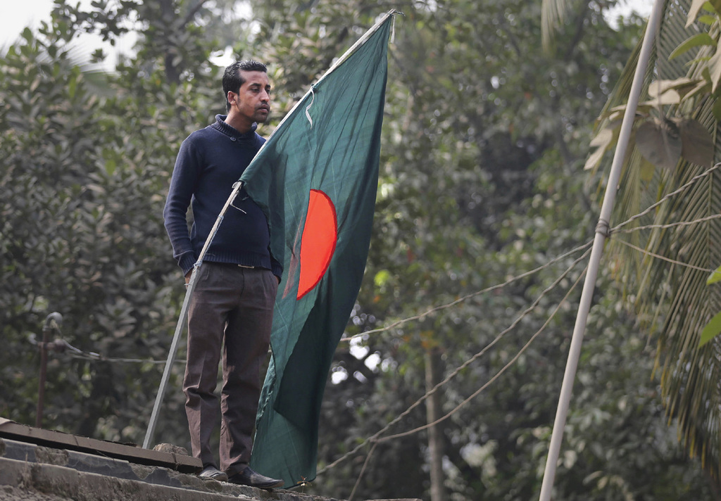 A man watches standing on the roof of his house the operation by Bangladeshi police to flush out suspected militants hiding in a buildi...