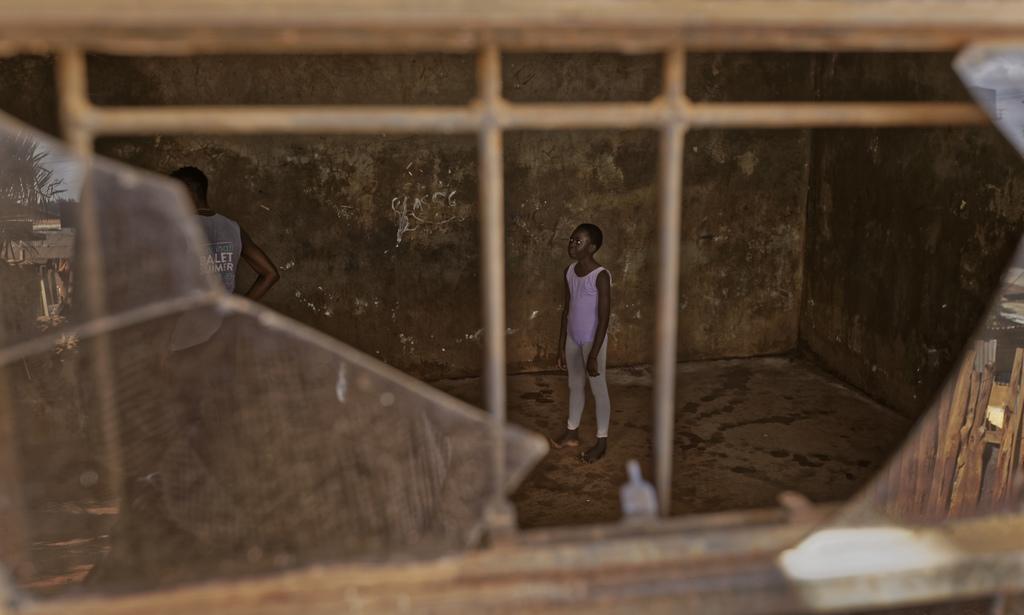 In this photo taken Friday, Dec. 9, 2016, a young ballerina waits for Kenyan ballet dancer Joel Kioko, 16, left, to teach a class in a ...