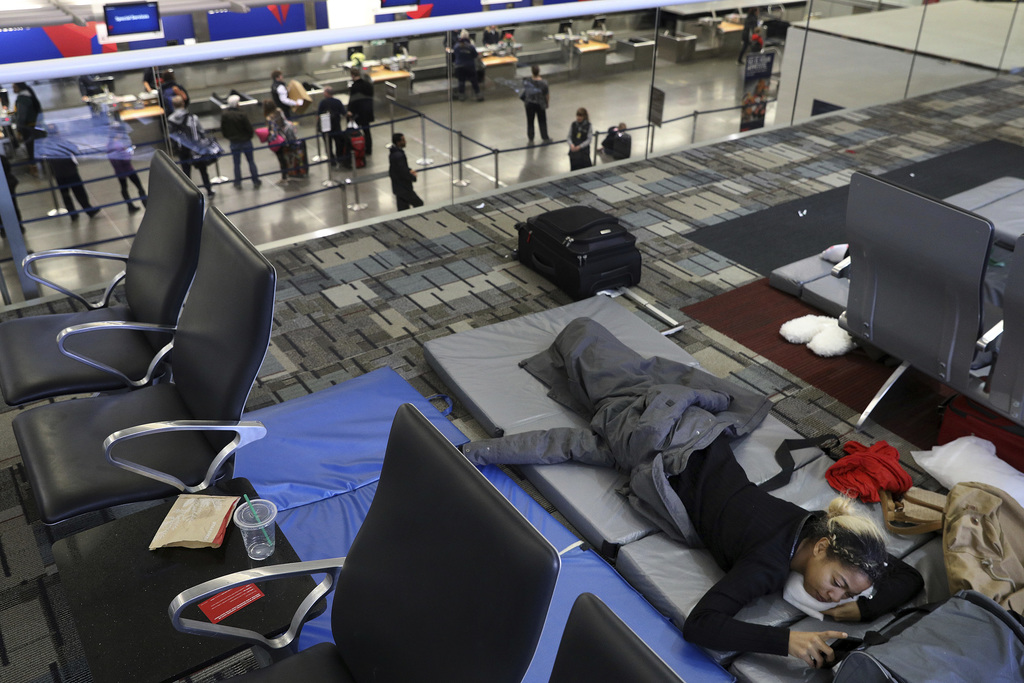 Makelah White, 20, lies on a mat while waiting to get a rescheduled flight to California after several flights were delayed or canceled...