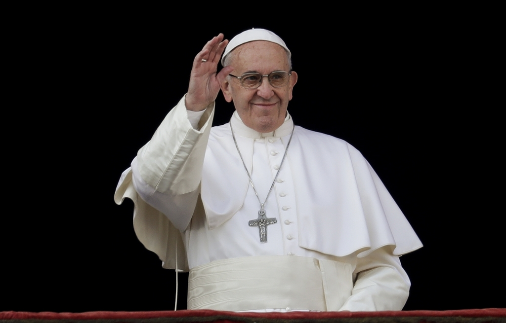 Pope Francis waves to faithful prior to delivering the Urbi et Orbi (Latin for ' to the city and to the world' ) Christmas' day blessin...