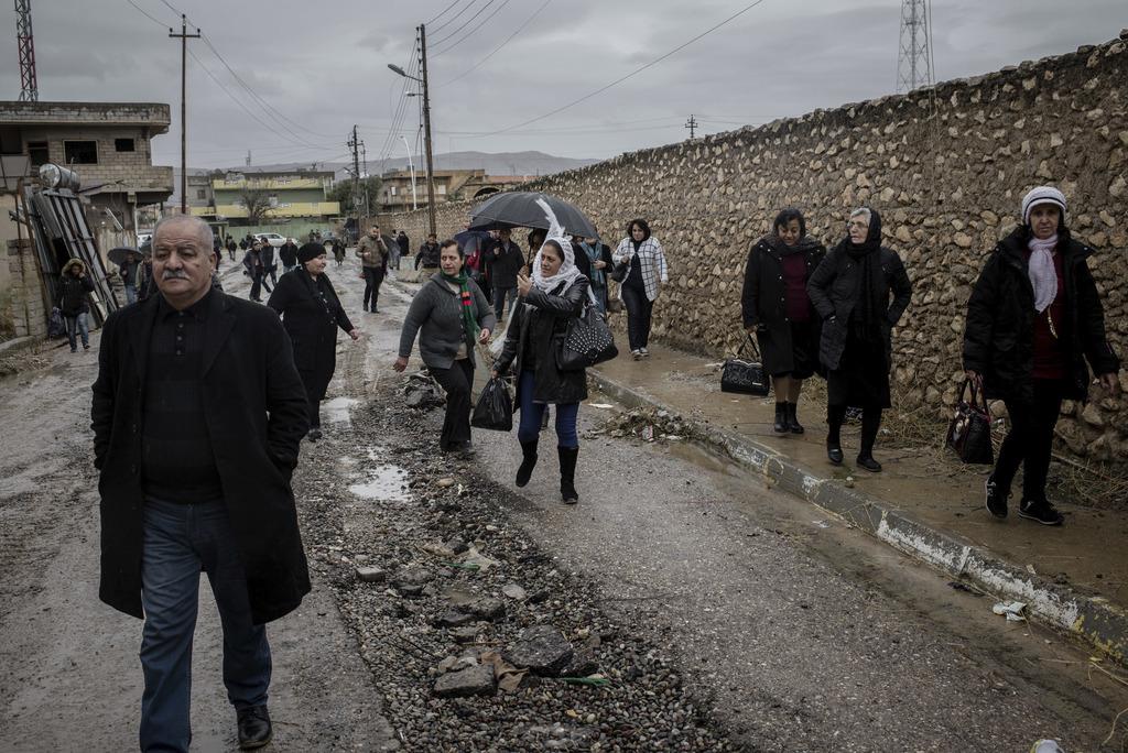 Christians walk in the rain to attend Christmas Eve's Mass in the Assyrian Orthodox church of Mart Shmoni, in Bartella, Iraq, Saturday,...
