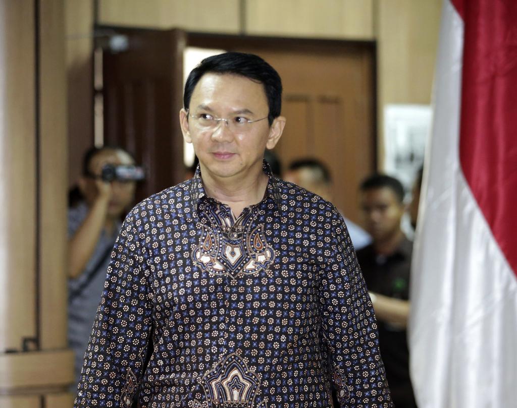 "Jakarta Governor Basuki Tjahaja Purnama, popularly known as ""Ahok,"" walks inside a court room for his trial at North Jakarta District C..."