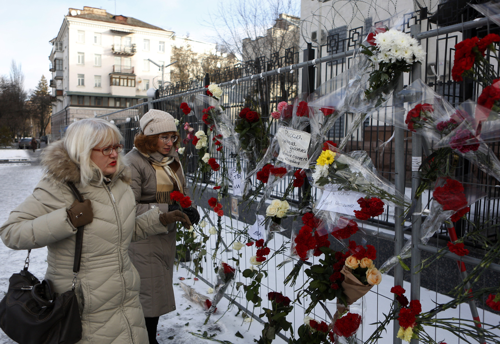 Women put flowers in front of the Russian embassy building in Kiev, Ukraine, Monday, Dec. 26, 2016. All 84 passengers and eight crew me...