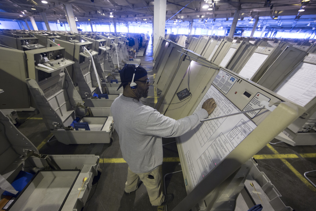 In this Oct. 14, 2016 photo, a technician works to prepare voting machines to be used in the upcoming election in Philadelphia. These p...