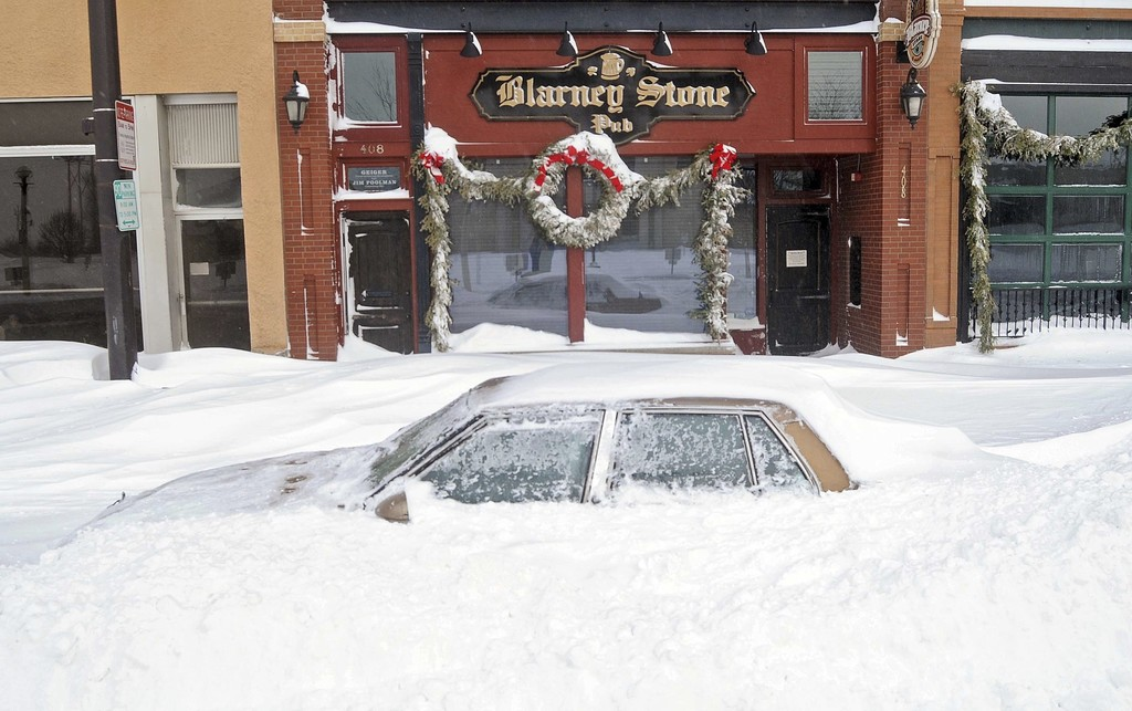 A car parked on a street in downtown Bismarck, N.D., is covered by a snowdrift on Monday, Dec. 26, 2016, after Sunday's Christmas Day b...