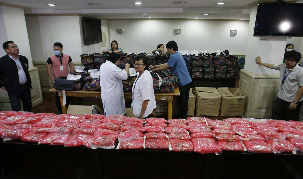Members of the National Bureau of Investigation arrange bags containing nearly one metric ton of seized methamphetamine during a press ...