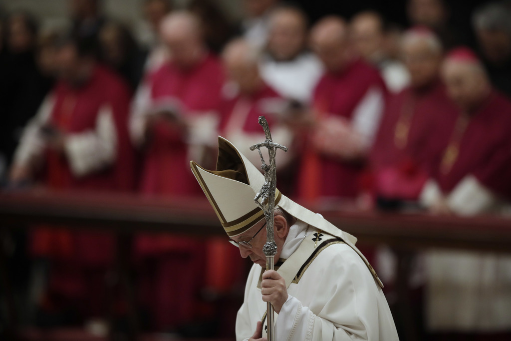Pope Francis bows in front of the altar as he celebrates the Christmas Eve Mass in St. Peter's Basilica at the Vatican, Saturday, Dec. ...
