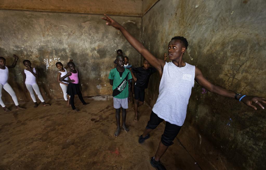 In this photo taken Friday, Dec. 9, 2016, young ballerinas receive instruction from Kenyan ballet dancer Joel Kioko, 16, right, in a ro...