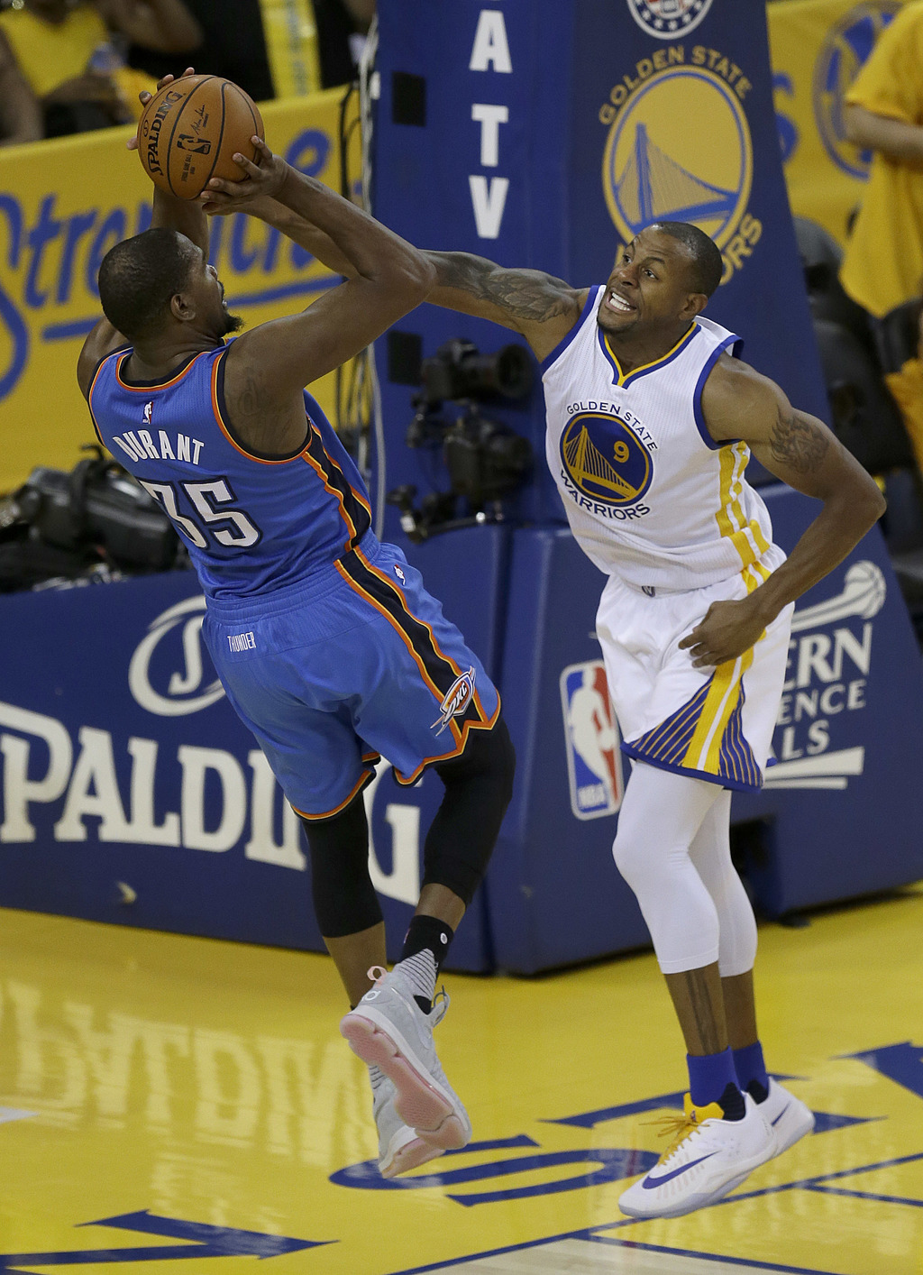 FILE - In this May 30, 2016, file photo, Oklahoma City Thunder forward Kevin Durant (35) shoots as Golden State Warriors forward Andre ...