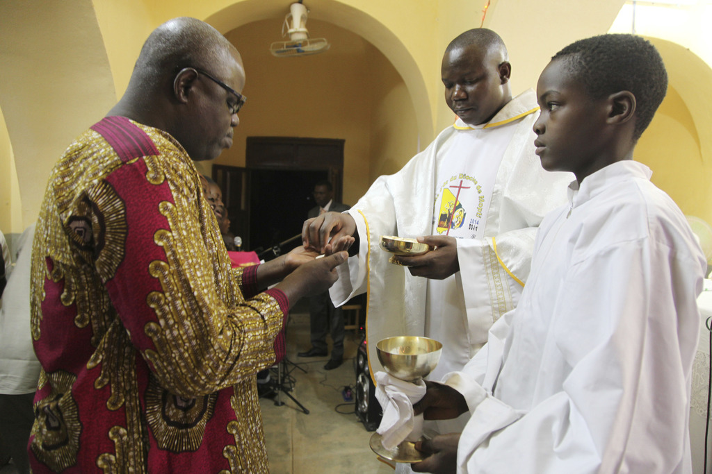 In this photo taken Saturday, Dec. 24, 2016, Anthero Afeku, a Catholic priest , centre, performs a communion mass to celebrate Christma...