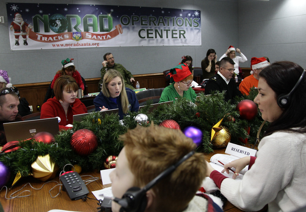 FILE - In this Dec. 24, 2012, file photo, volunteers take phone calls from children asking where Santa is and when he will deliver pres...