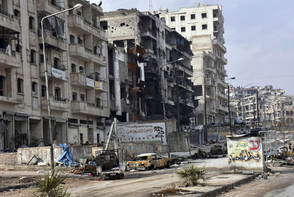 This photo released by the Syrian official news agency SANA, shows damaged buildings and cars in the Ansari neighborhood, east Aleppo, ...