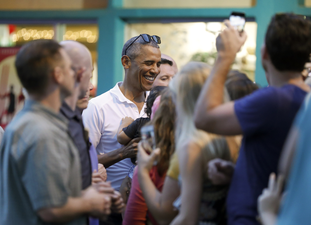 President Barack Obama greets people waiting for him outside Island Snow Hawaii in Kailua, Hawaii, Saturday, Dec. 24, 2016, after the p...