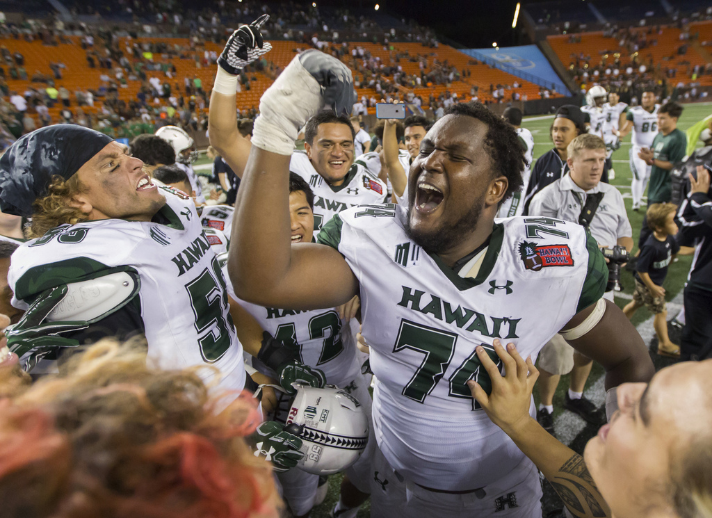 Hawaii offensive lineman RJ Hollis (74) and his teammates celebrate after defeating Middle Tennessee 52-35 in the Hawaii Bowl NCAA coll...