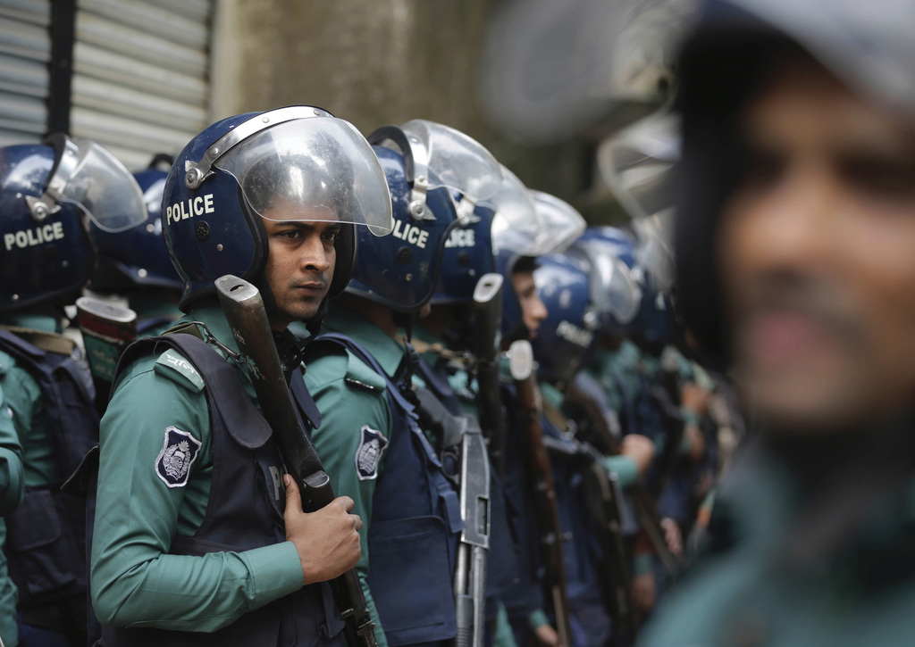 Bangladesh policemen stand guard after cordoning off the building where suspected militants are hiding, in Dhaka, Bangladesh, Saturday,...