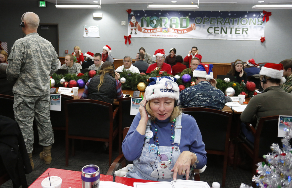 FILE - In this Dec. 24, 2014, file photo, volunteers take phone calls from children asking where Santa is and when he will deliver pres...