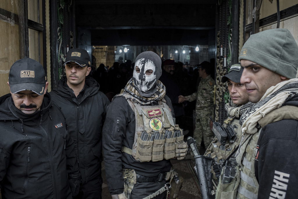 Iraqi forces guard the entrance to a Christmas Eve's Mass at the Assyrian Orthodox church of Mart Shmoni, in Bartella, Iraq, Saturday, ...