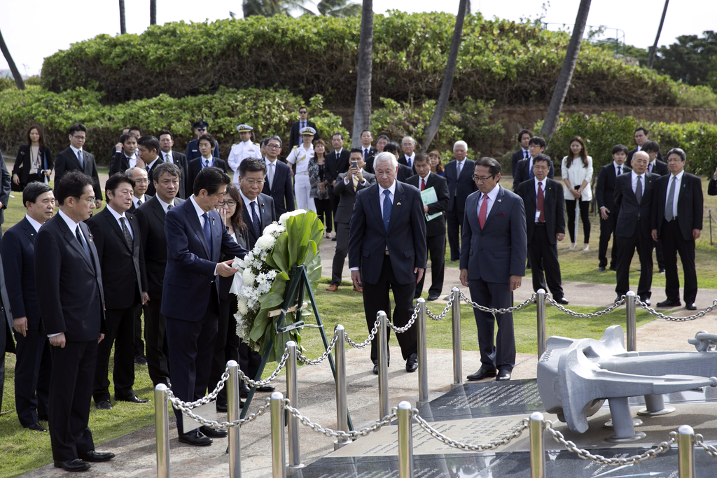 Japanese Prime Minister Shinzo Abe, center, lays a wreath at the Ehime Maru Memorial at Kakaako Waterfront Park, Monday, Dec. 26, 2016,...