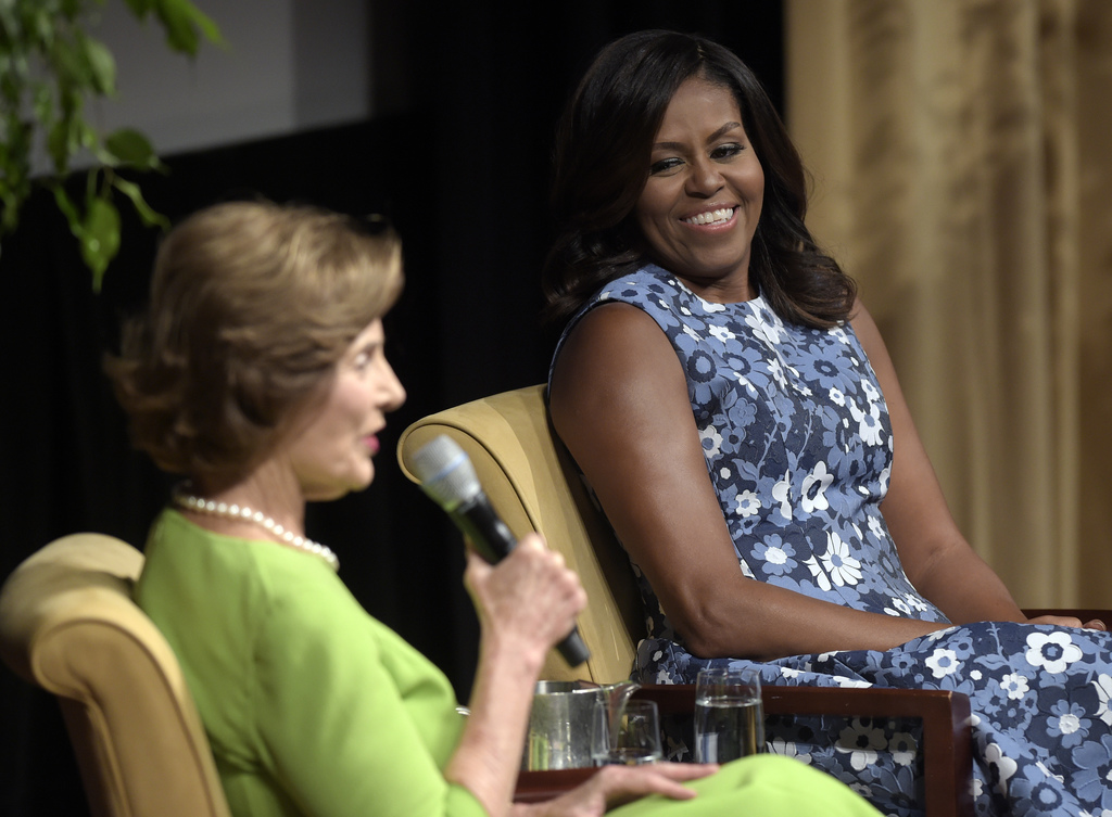 """FILE - In this Sept. 16, 2016, file photo, first lady Michelle Obama listens as former first lady Laura Bush speaks during the """"America..."""