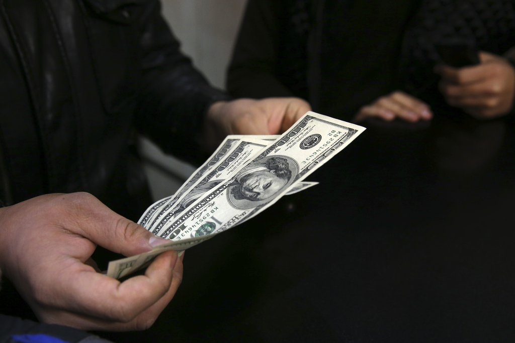 In this picture taken on Monday, Dec. 26, 2016, a customer counts U.S. dollars in a currency exchange bureau in downtown Tehran, Iran. ...