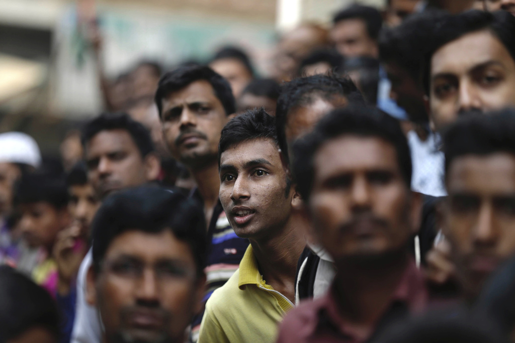 Bangladesh people watch as policemen surround the building where suspected militants are hiding in Dhaka, Bangladesh, Saturday, Dec. 24...