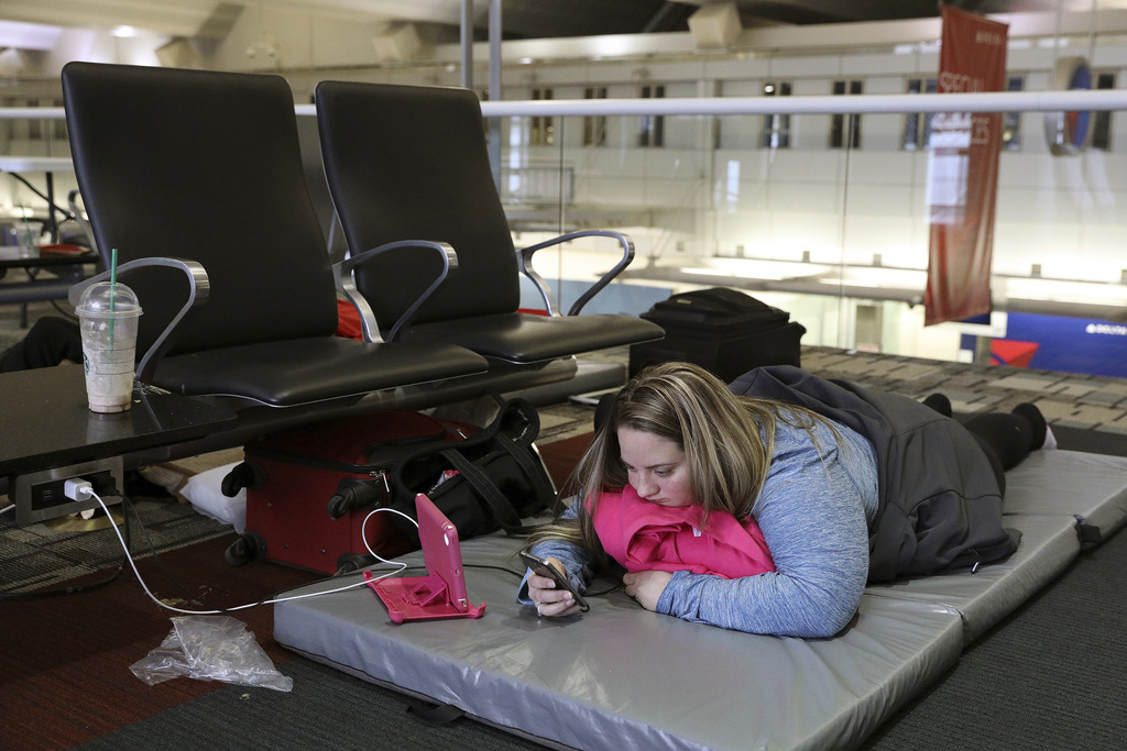 Chelsey Kalmback, 29, plays on her phone while waiting for a rescheduled flight to North Dakota after several flights were delayed or c...