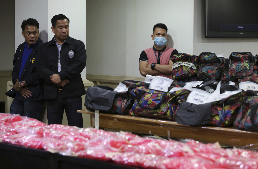 Members of the National Bureau of Investigation stand guard near bags containing nearly one metric ton of seized methamphetamine during...