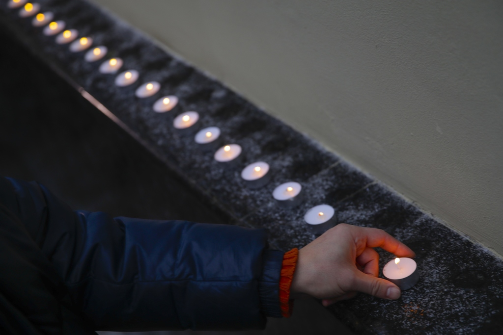 A man places a candle at the well-known military choir's building in Moscow, Russia, Sunday, Dec. 25, 2016, after a plane carrying 64 m...