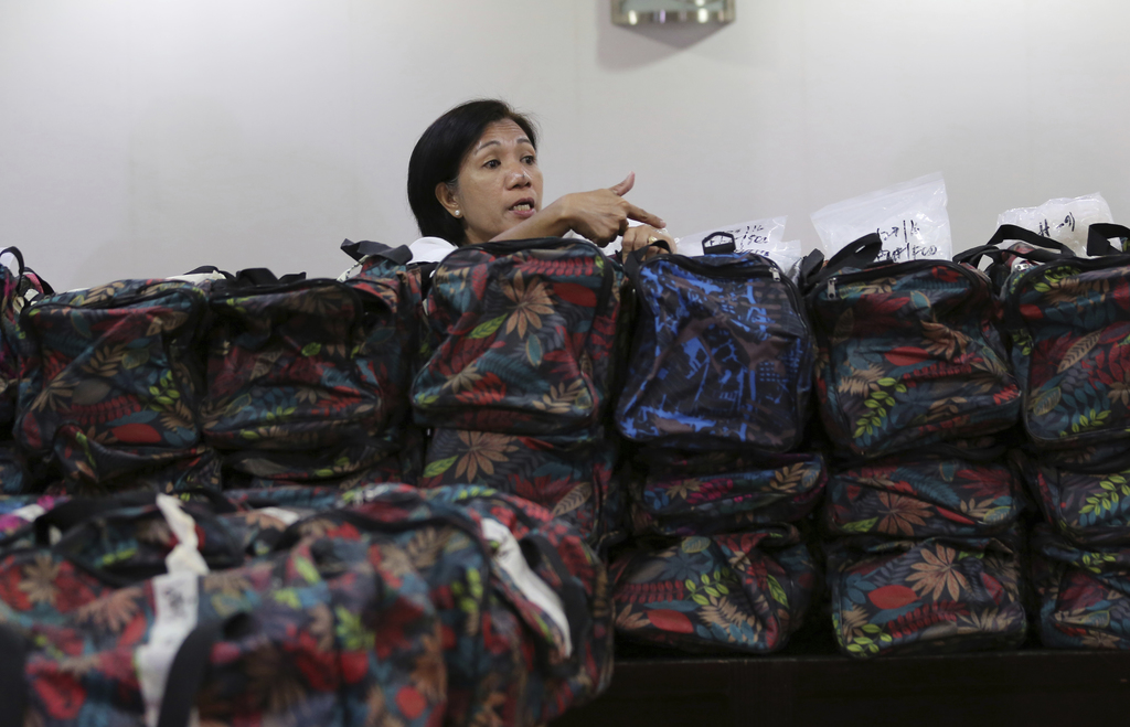 A member of the National Bureau of Investigation arranges bags containing nearly one metric ton of seized methamphetamine during a pres...