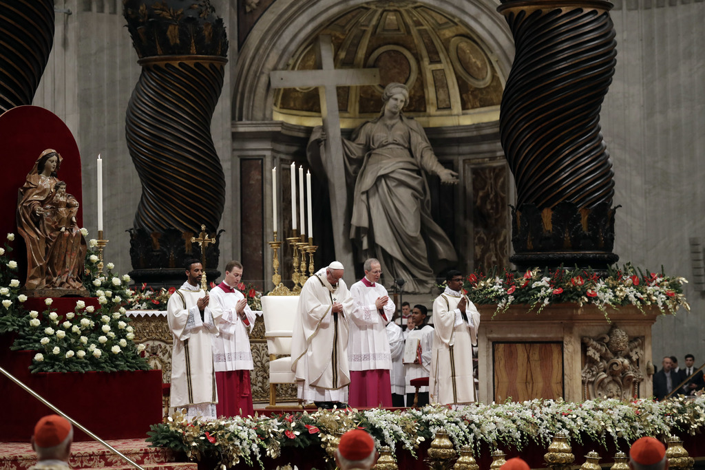 Pope Francis, background center, celebrates the Christmas Eve Mass in St. Peter's Basilica at the Vatican, Saturday, Dec. 24, 2016. (AP...