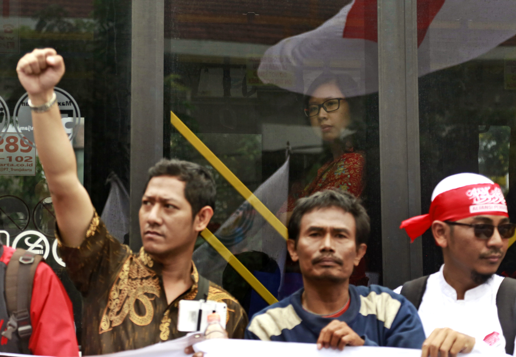"""A passenger looks out from a passing bus as Muslim men stage a protest against Jakarta Governor Basuki """"Ahok"""" Tjahaja Purnama outside t..."""