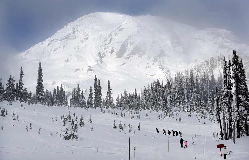 In this photo taken Friday, Dec. 16, 2016, Mount Rainier fills the sky behind as a group of snowshoers head out of the Paradise area fo...