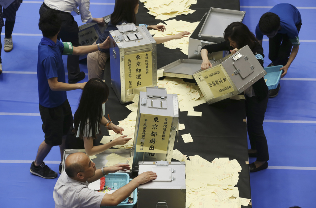 FILE - In this Sunday, July 10, 2016 file photo, election workers open ballot boxes to count votes for the upper house elections at a b...