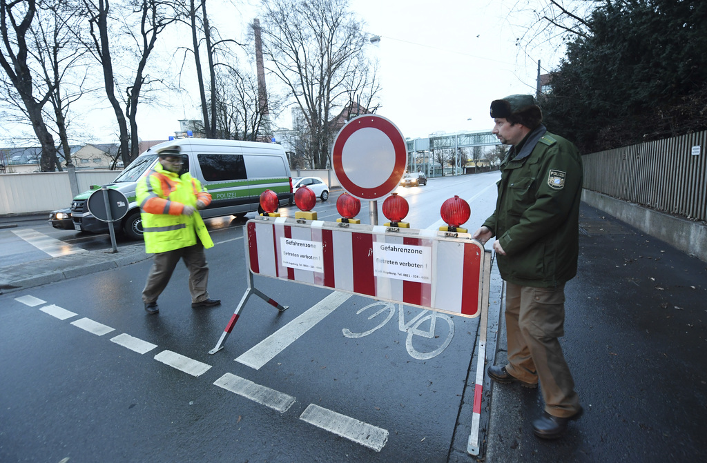 Policemen have blocked a road in Augsburg, Germany, Sunday, Dec. 25, 2016. Thousands of people in the German town of Augsburg have temp...