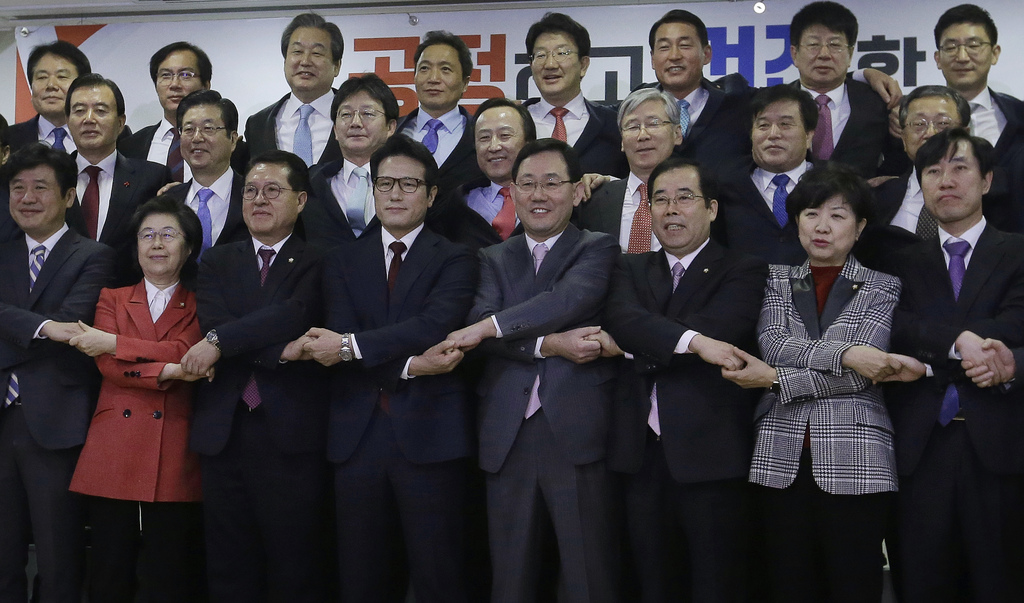 A group of lawmakers of the ruling Saenuri Party joins their hands during a press conference to announce to leave the party at the Nati...
