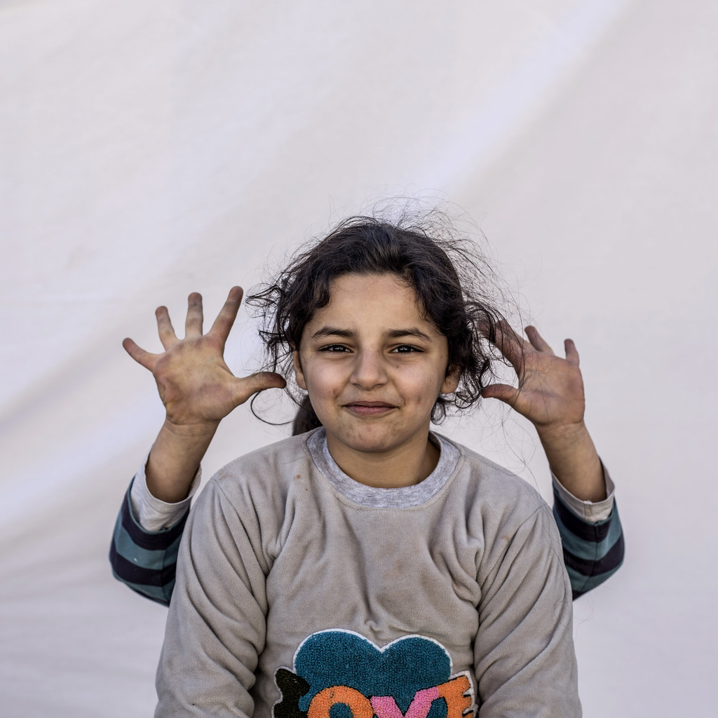 Mariam Saad, 7, and a friend play while posing for a portrait in a camp where Christians displaced by Islamic State militants are livin...