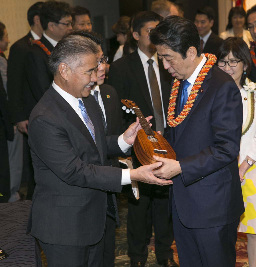 Hawaii Gov. David Ige, left, presents Japanese Prime Minister Shinzo Abe a pineapple-shaped ukulele at a dinner held in Abe's honor, Mo...