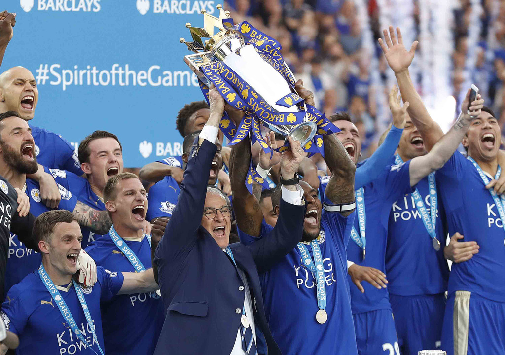 FILE- In this May 7, 2016, file photo, Leicester's team manager Claudio Ranieri and Leicester's Wes Morgan lift the trophy as Leicester...