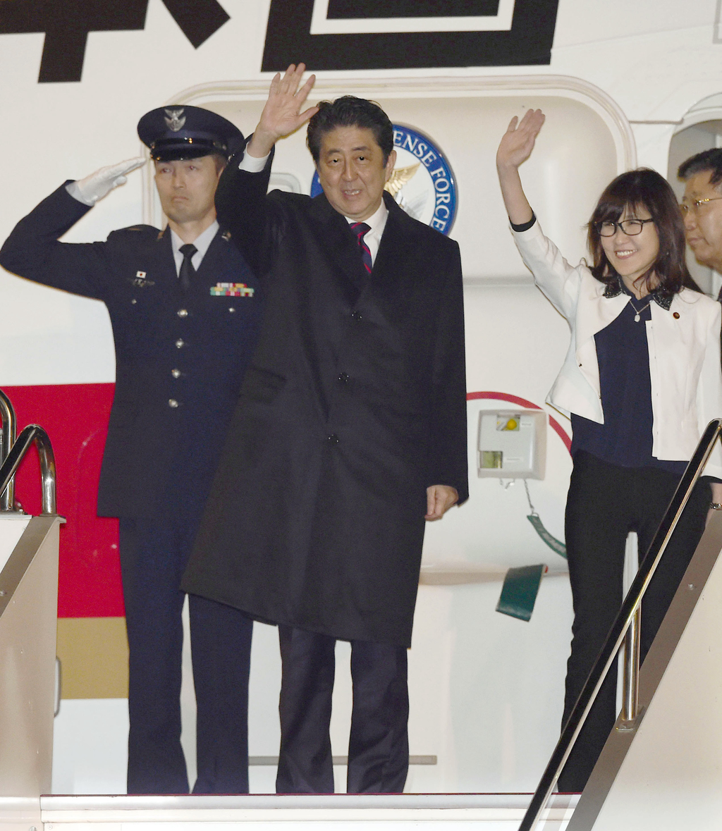 Japanese Prime Minister Shinzo Abe, second left, and Defense Minister Tomomi Inada, second right, wave before their departure for Hawai...