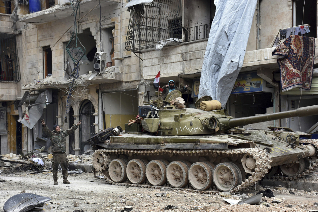 This photo released by the Syrian official news agency SANA, shows Syrian army soldiers flash the victory sign near their tank in the S...