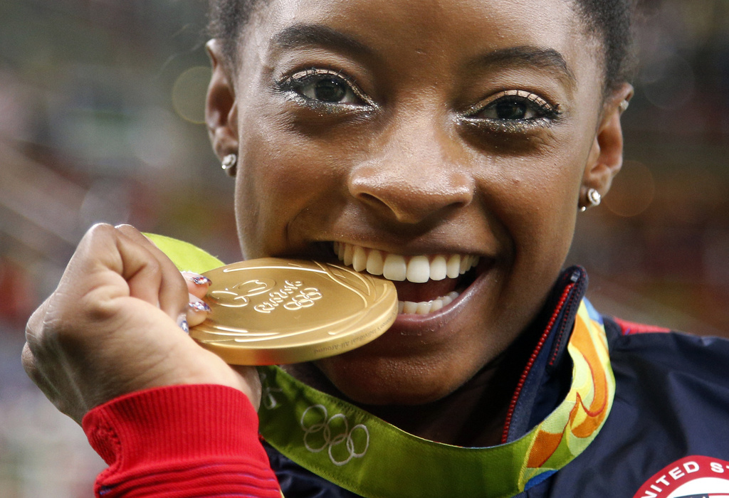 FILE - In this Aug. 11,2 016 file photo, United States' Simone Biles bites her gold medal for the artistic gymnastics women's individua...